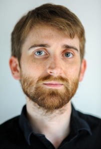 A photograph of Ian Bowkett. We can see his head and shoulders. He has short light-brown hair, a short beard and blue eyes. He is wearing a black shirt and is standing against a pale blue background.