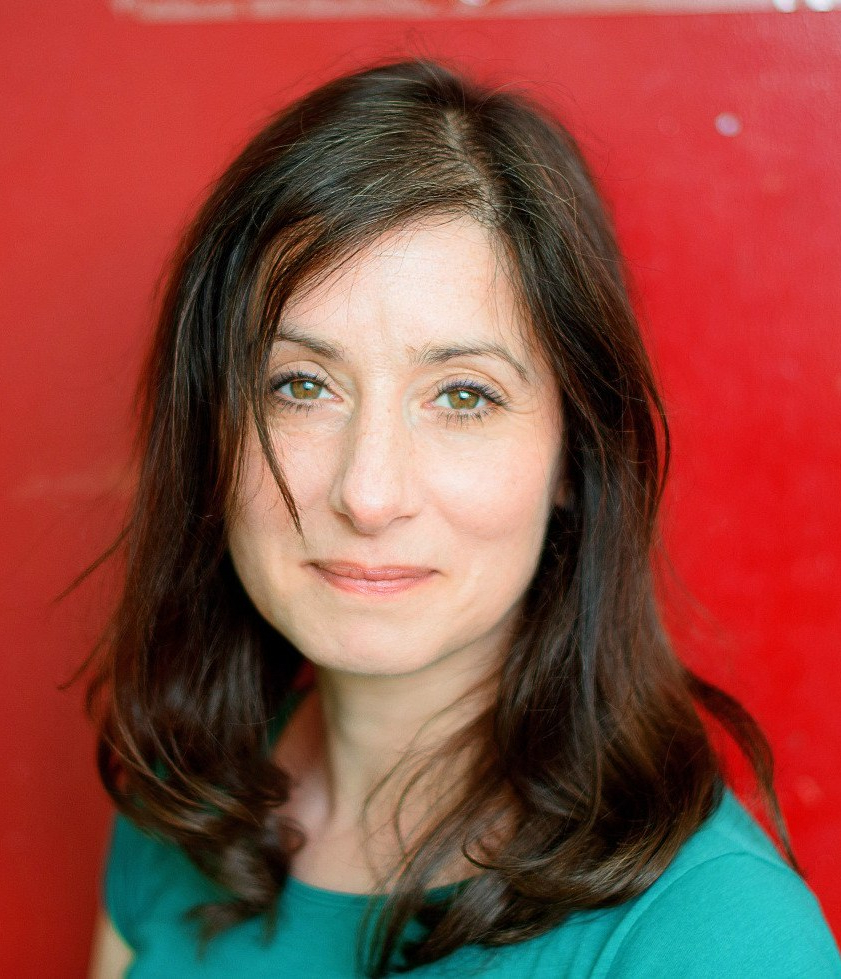 A photograph of Rachel Souhami. We can see her head and shoulders. She has shoulder-length brown hair, is wearing a green t-shirt and is standing in front of a red background.